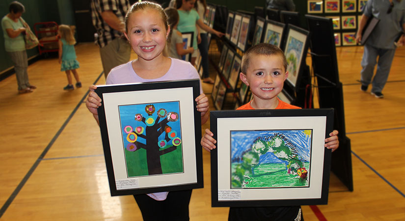 Students holding their art work.