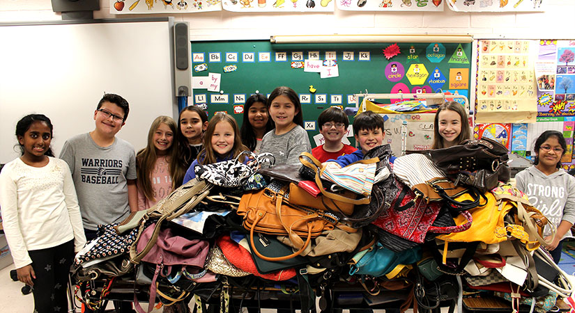 Students standing in front of handbags.